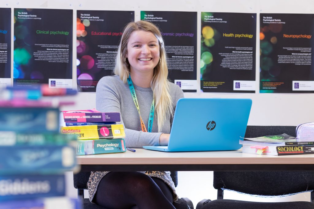 Student smiling while sitting at desk with laptop and books
