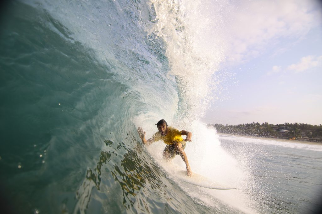 Surfer making his way into a blue water barrel