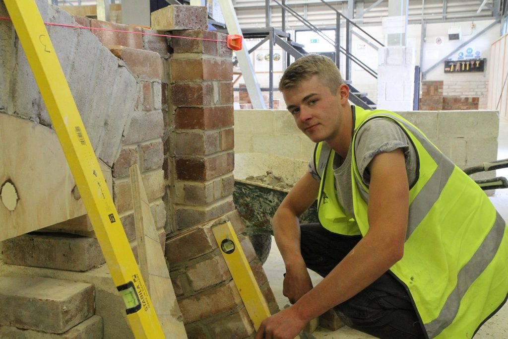 Bricklaying student building a wall in the workshop