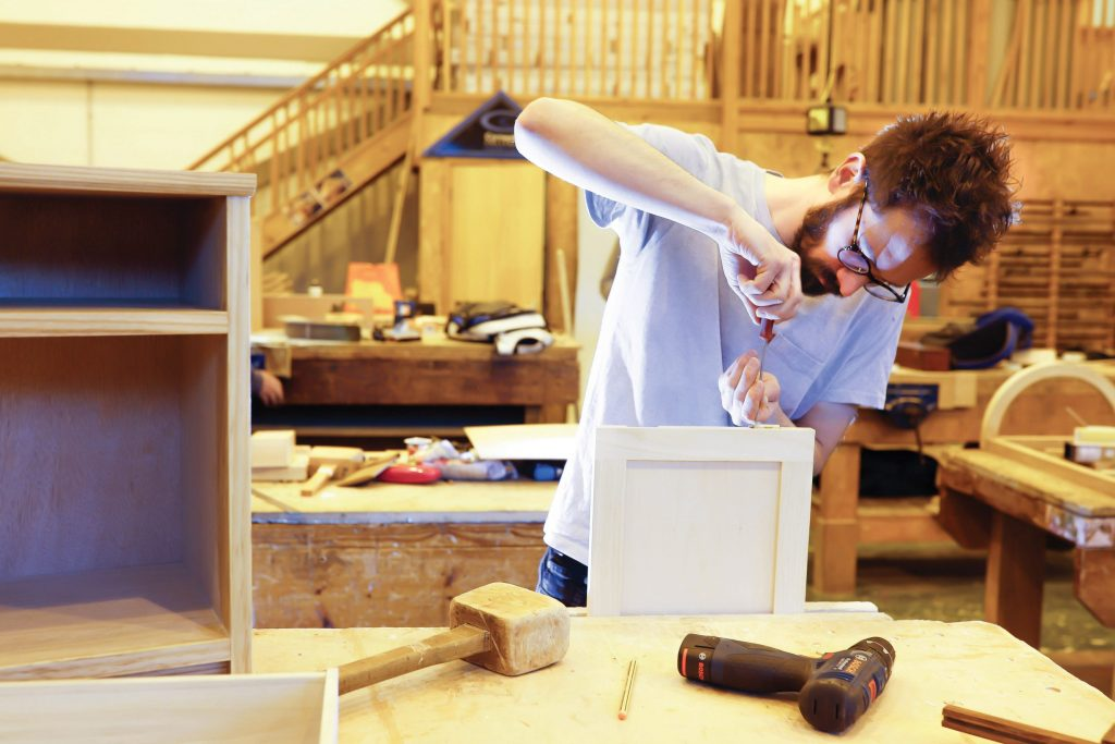 Furniture student working on a piece in workshop