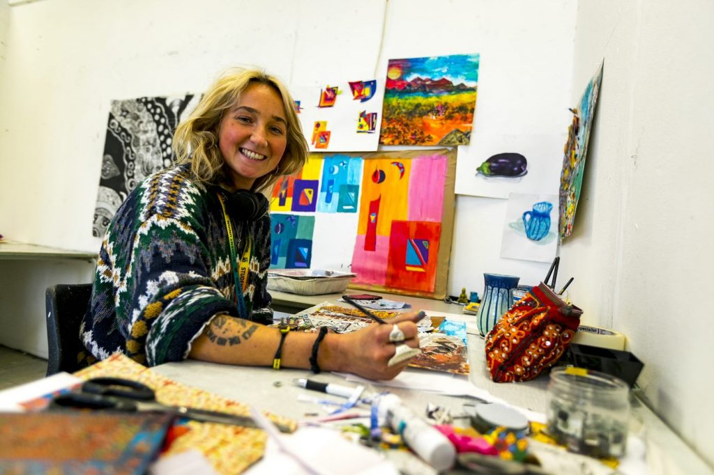 Art &Design student at Camborne campus, surrounded by paintings