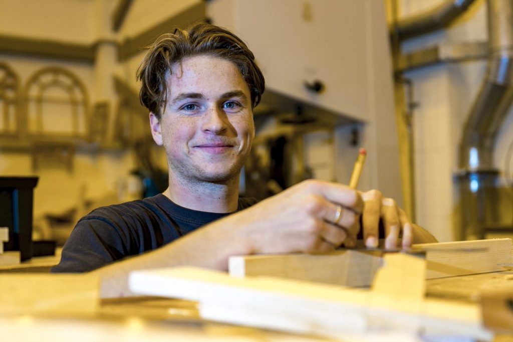 Man smiling while standing in front of wood pieces