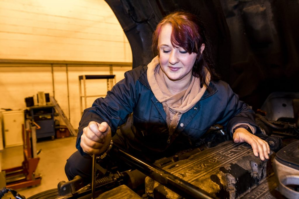 Female automotive student working on car