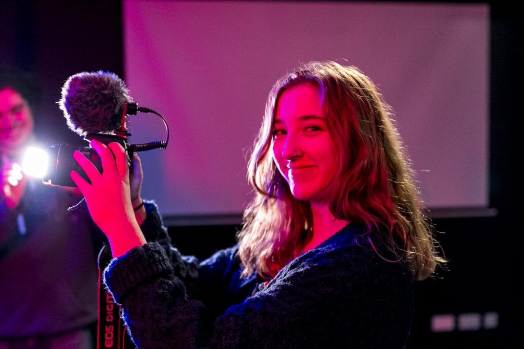 Female student holding a camera with a microphone