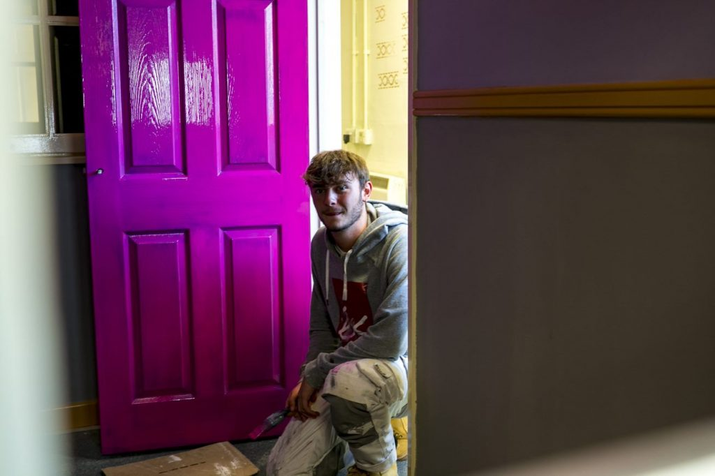 Painting and Decorating student sitting next to newly painted purple door