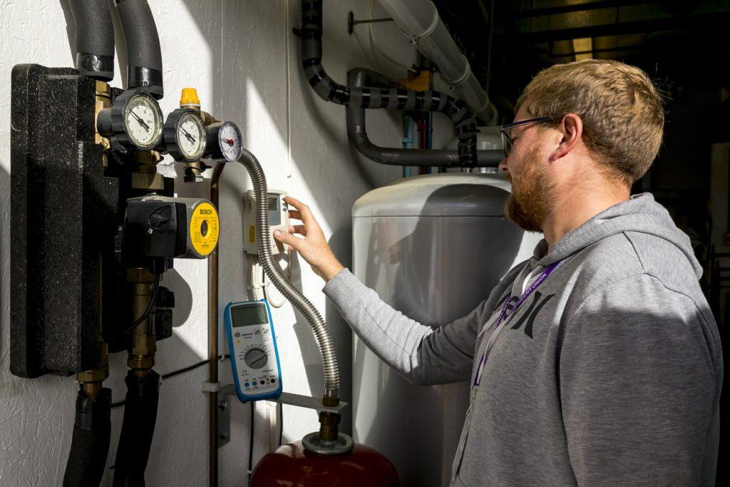 Man checking plumbing meters