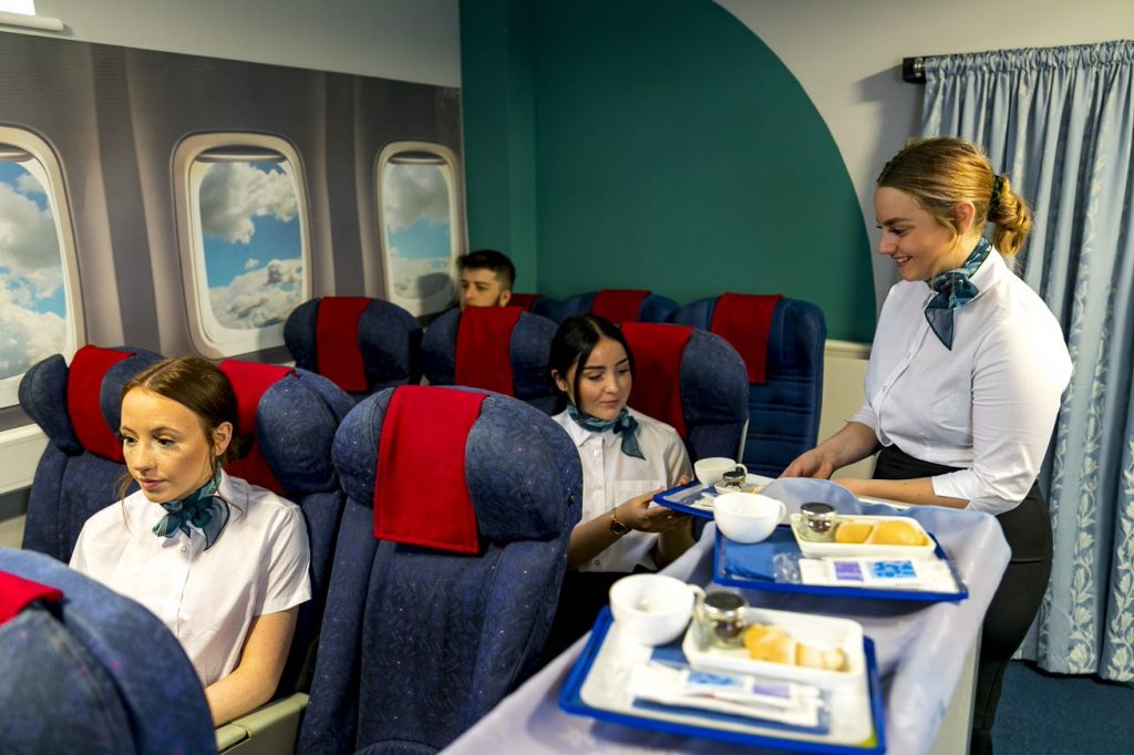 Travel and tourism students in airplane simulator in classroom