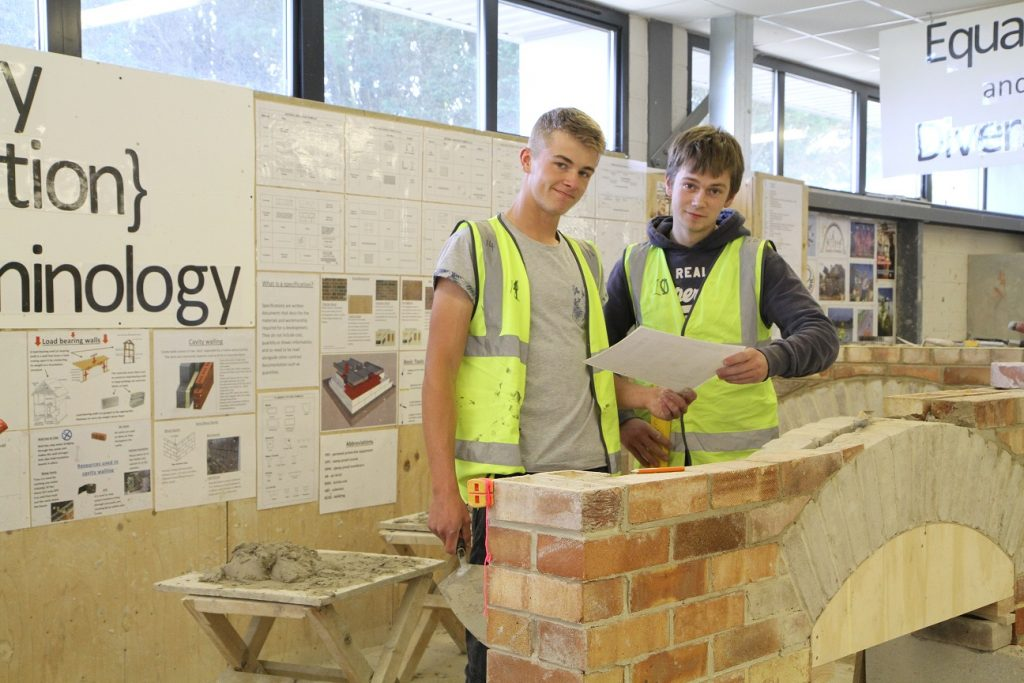 Two students building a wall in the construction workshop
