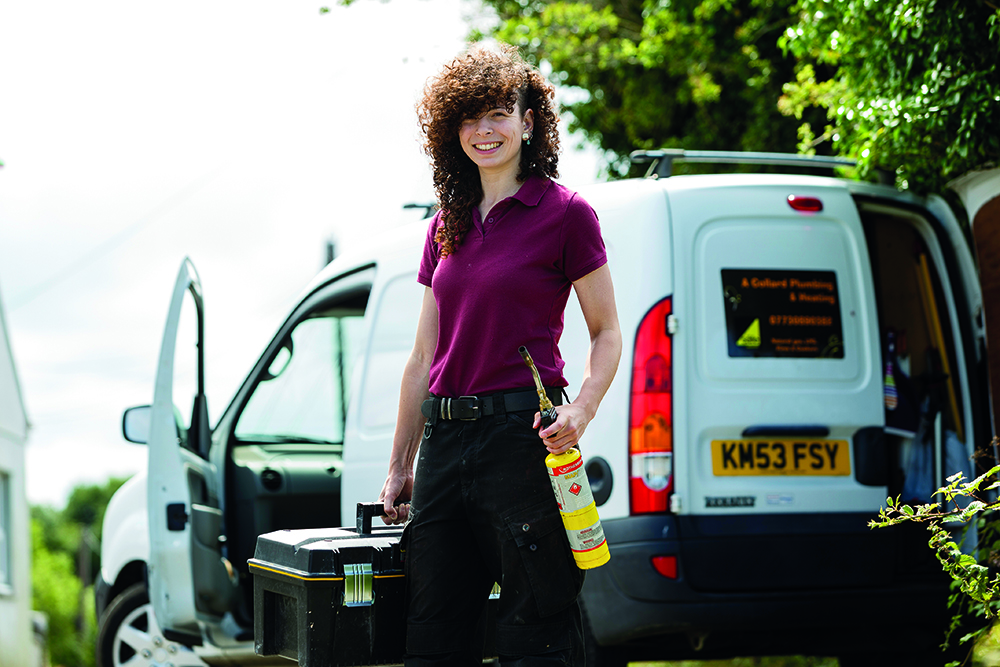 Female student smiling while standing in front of white van