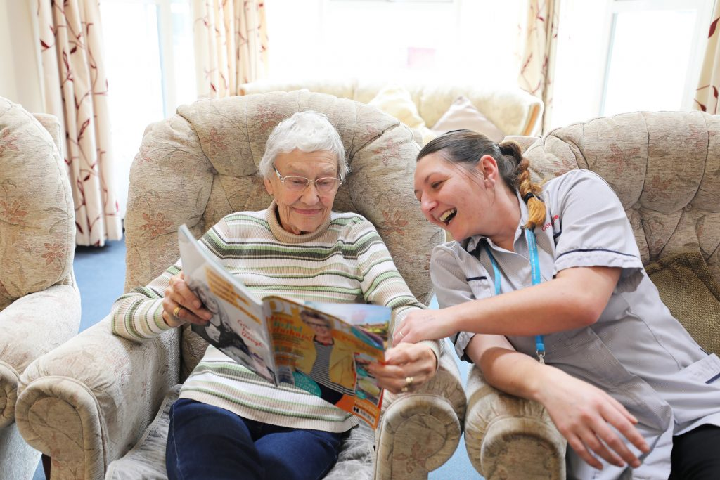 Female caregiver and elderly woman reading together
