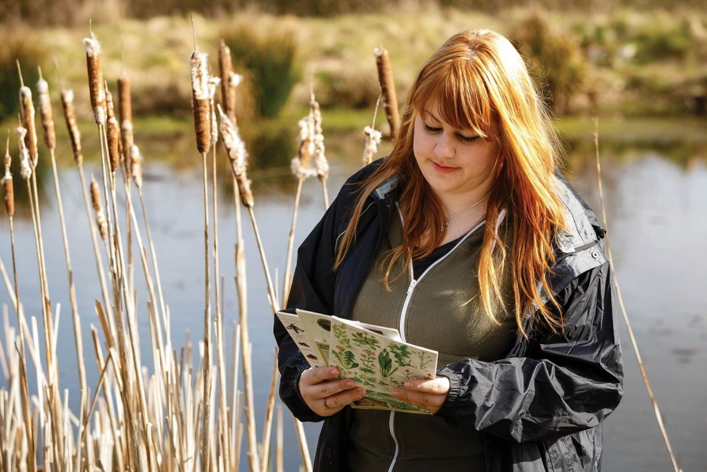 Woman looking at leaflets while standing in front of lake