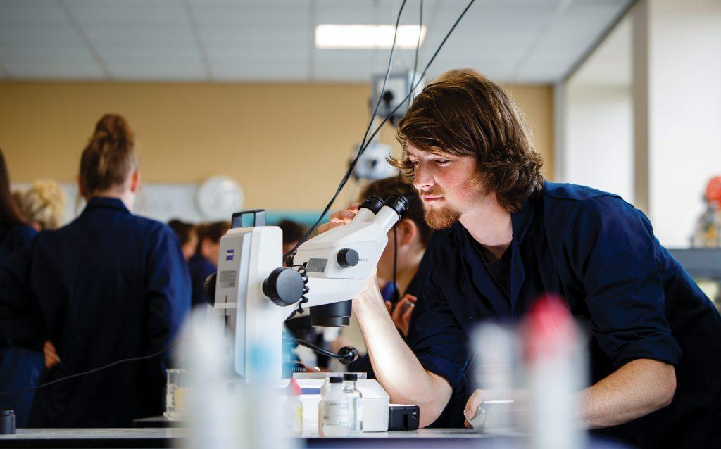 Man using microscope in classroom